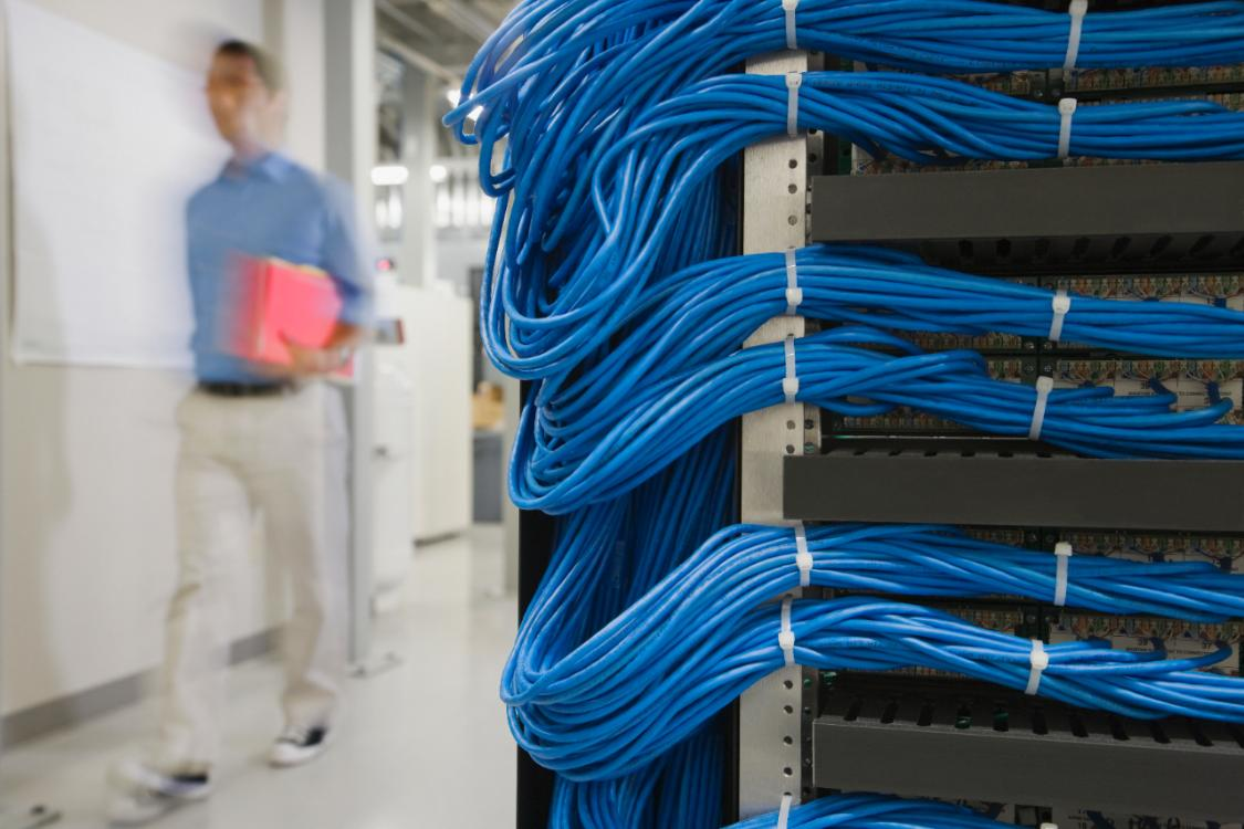 blue network cables with man walking past