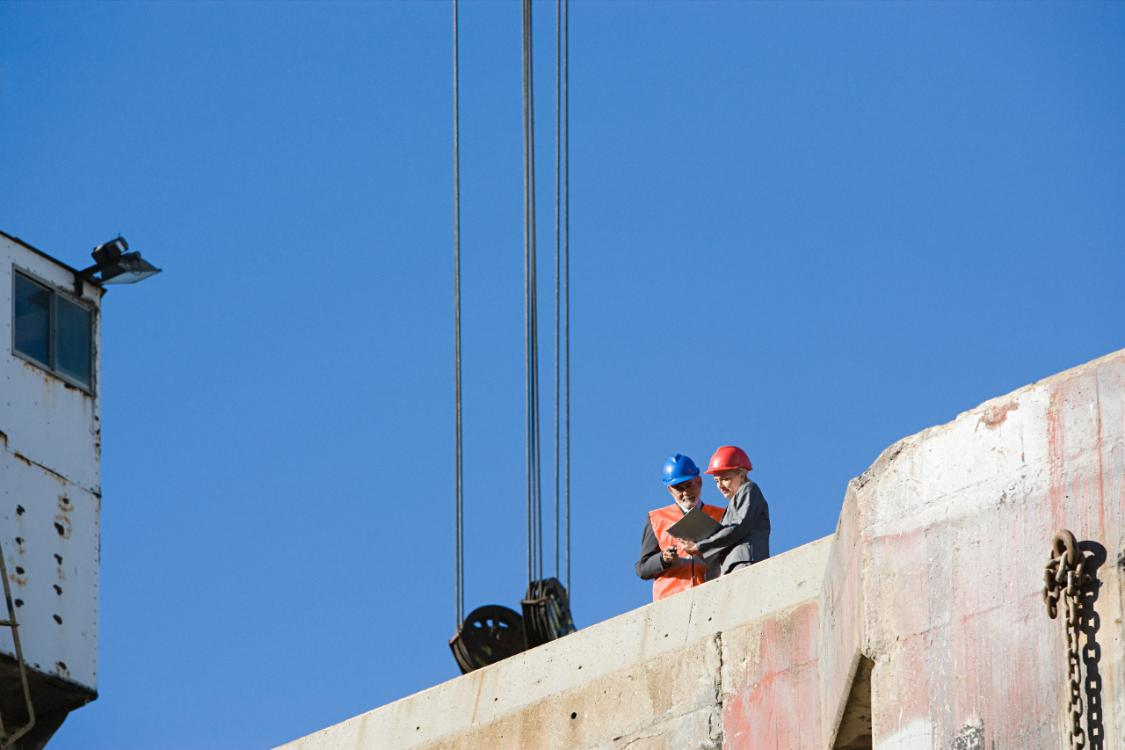 two workers standing on construction site