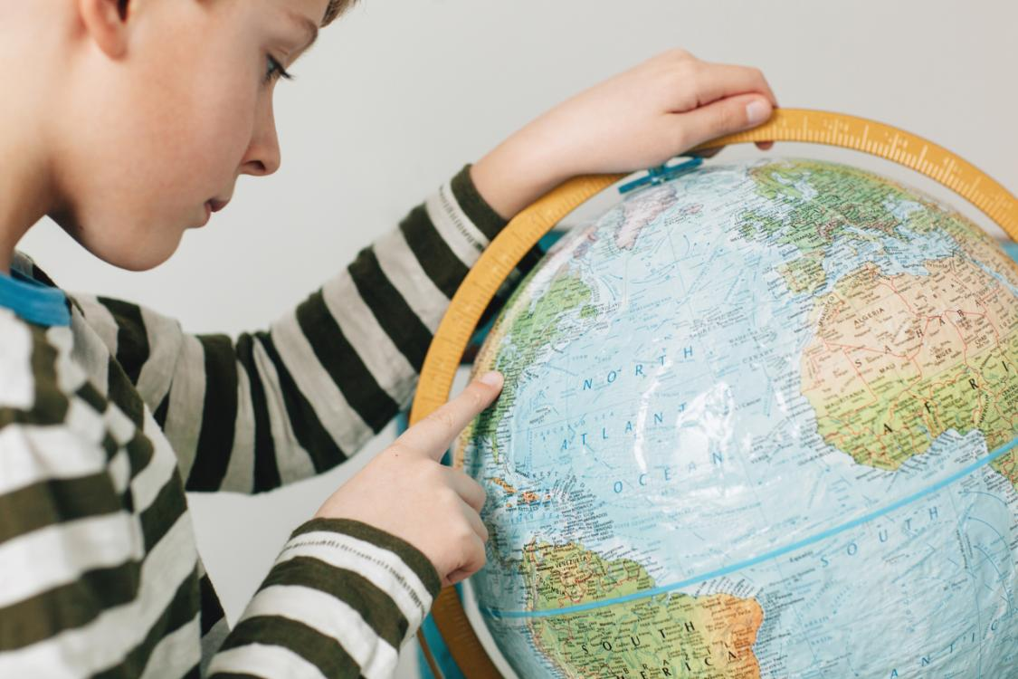 child looking at globe of the world