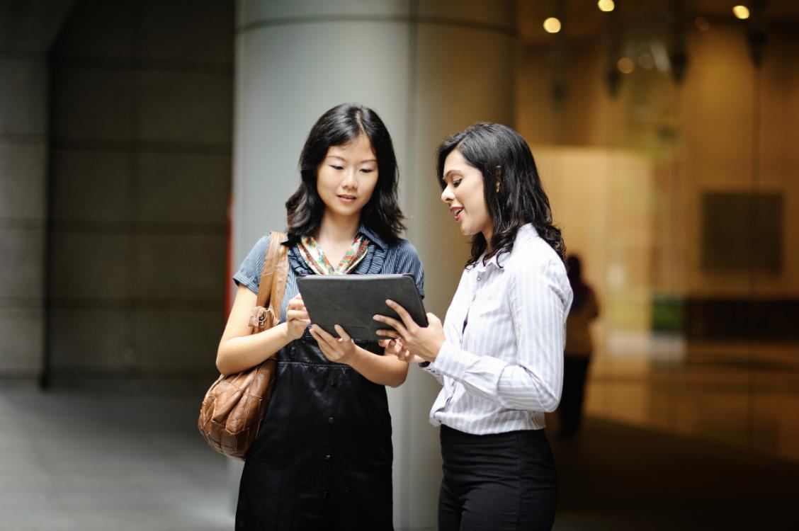 two women looking at a tablet together