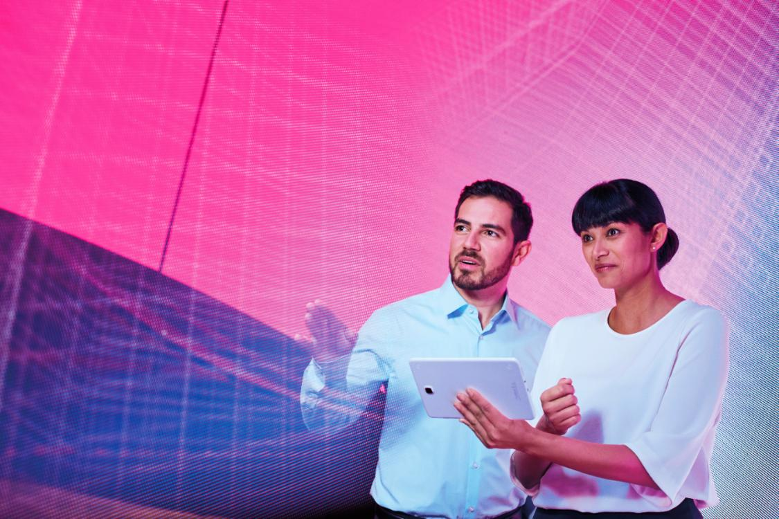 man and women with tablet against backdrop of neon pink lights
