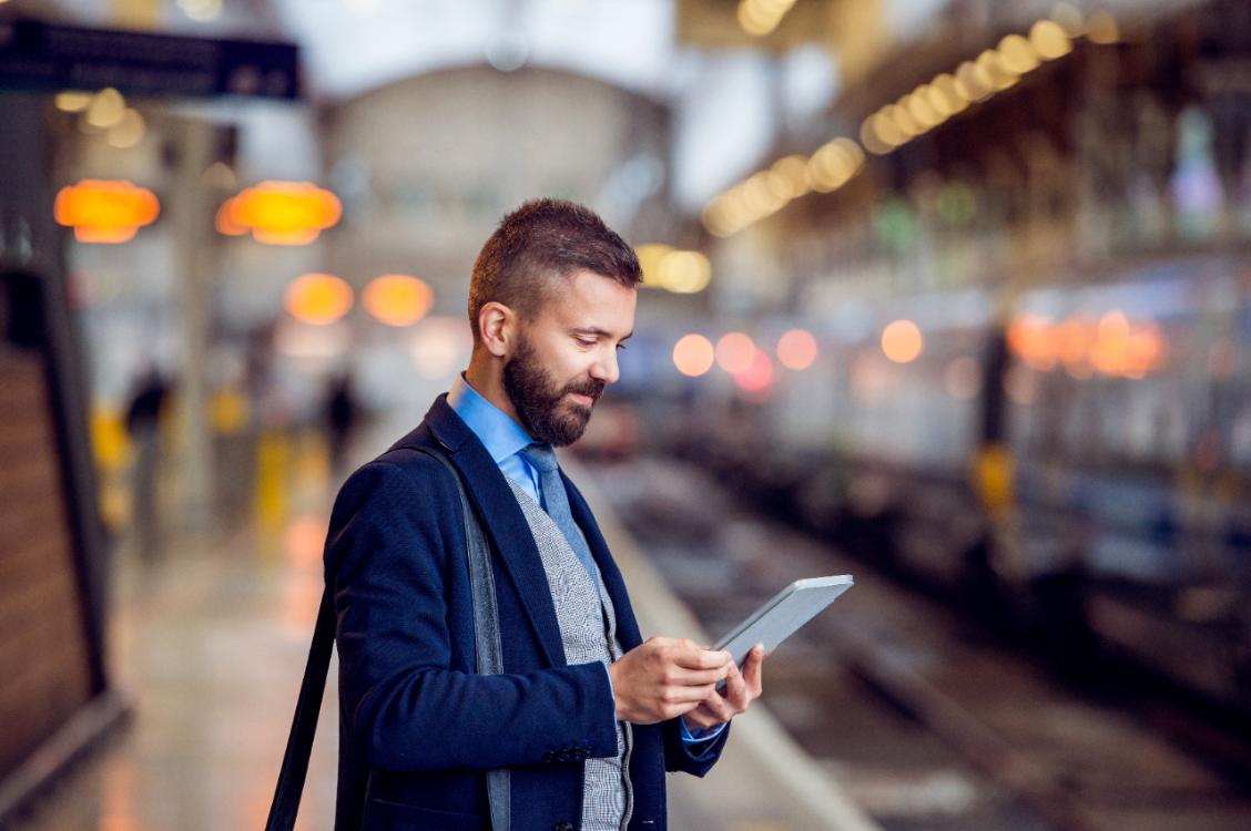 man standing on train platform whilst using tablet